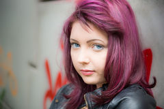 Sad teen girl. Leans up against graffiti covered wall outside school Stock Images