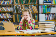 Sad teen girl in the library Stock Photography