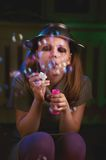 Sad teen girl sits and blows soap bubbles Stock Images