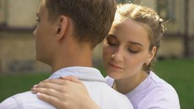 Sad teen girlfriend hugging boyfriend and looks at camera, relation difficulties stock video footage