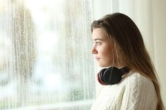 Sad teen with headphones looking through a window. Side view portrait of a sad teen with headphones looking through a window in a rainy day Royalty Free Stock Photography