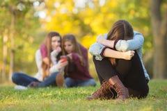 Sad Teen Hiding Face. Sad teenage women sitting with head down near laughing group Stock Image