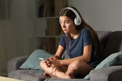 Sad teen listening to music alone at home. Full body portrait of a sad teen listening to music alone sitting on a couch in the living room at home Stock Photography