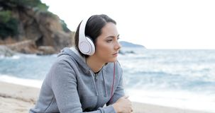 Sad teen listening to music on the beach. Sad teenage girl listening to music from a smart phone and watching ocean on the beach stock footage