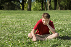 Sad Teen Looking Down. Sad young Caucasian male sitting on grass Stock Photos