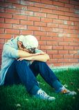 Sad Teenager outdoor. Sad Teen near the Brick Wall of the House Royalty Free Stock Image