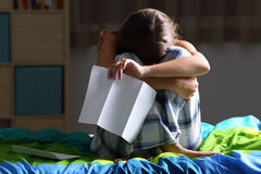 Sad teen after reading a letter. Front view of a single sad teen lamenting sitting on her bed after reading a letter with a dark light in the background Royalty Free Stock Photography