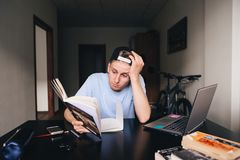 A sad teen reads a book at the desk near the computer in his room. Teaching at home. The student does not want to read the book Royalty Free Stock Photo