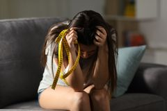 Sad teen worried about appearance holding a measure tape stock photo
