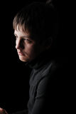 Sad teenage boy in black, low key. Sad teenage boy is photographed on the black background. He is upset. She is wearing in black Stock Photo