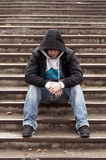 Sad teenage boy with hood sitting on stairs. Close up royalty free stock photography