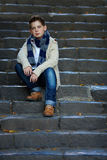 Sad teenage boy sit on stone stairs outdoor Stock Image