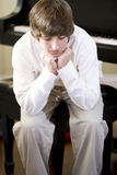 Sad teenage boy sitting with chin on hands Royalty Free Stock Photo