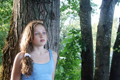 Sad Teenage Girl. Beautiful sad young girl leaning against a tree Royalty Free Stock Photography