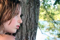 Sad Teenage Girl. Close-up of a beautiful sad young girl with her face against a tree Stock Images