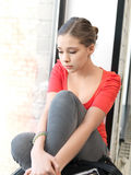 Sad teenage girl. Bright indoors picture of calm teenage girl royalty free stock photography