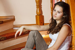 Sad teenage girl. Portrait of a beautiful teenage girl with long brown hair, sitting on stairs at home looking depressed Royalty Free Stock Photography