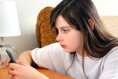 Sad Teenage Girl. With Mobile phone at the Home Stock Image