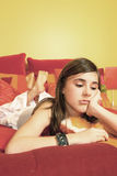 Sad teenage girl on bed. A view of a sad teenage girl lying on a bed Royalty Free Stock Photo