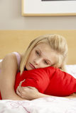 Sad Teenage Girl In Bedroom Hugging Pillow. On bed royalty free stock photos