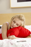 Sad Teenage Girl In Bedroom With Mobile Phone. Looking away from camera royalty free stock image