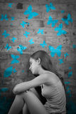 Sad teenage girl with blue butterflies. Sad teenage girl in black and white with blue butterflies painted on a brick wall stock photography