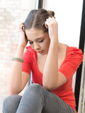 Sad teenage girl. Bright indoors picture of calm teenage girl stock image