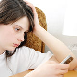 Sad Teenage Girl with Cellphone. At the Home Stock Photography