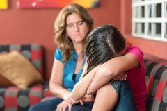Sad teenage girl cries next to her worried mother Stock Photos