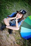 Sad teenage girl on ground beside umbrella