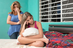 Sad teenage girl and her worried mother at home Stock Images