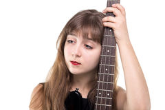 Sad teenage girl holding a guitar, looking up. On white background royalty free stock image