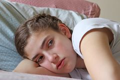 Sad teenage girl lying in bed before going to sleep stock photos