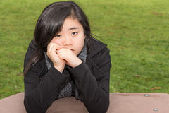 Sad Teenage Girl in Park. Young Asian American woman with expressive, sad eyes sitting with her face resting on her hands and her elbows on a picnic table in a Stock Photos