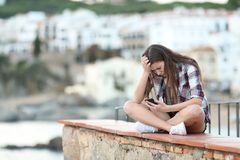 Sad teenage girl reading phone content on a ledge. Sad teenage girl reading smart phone content sitting on a ledge in a coast town stock image