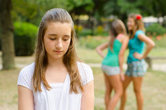 Sad teenage girl rejected by other teenage girls in park. Young depressed girl rejected by other teenage girls standing in park on beautiful summer day Stock Photo