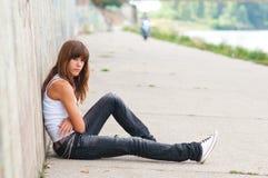 Sad teenage girl sitting alone. Cute sad teenage girl sitting alone in urban environment Stock Photography