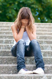 Sad teenage girl sitting alone on the stairs Royalty Free Stock Photo