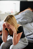 Sad Teenage Girl Sitting In Bedroom Whilst Boyfriend Sleeps Stock Photography