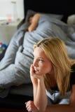 Sad Teenage Girl Sitting In Bedroom Whilst Boyfriend Sleeps. Sad Teenage Girl Sitting In Bedroom Looking Away From Camera Whilst Boyfriend Sleeps stock photos
