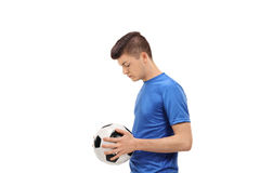 Sad teenage soccer player holding a football. Profile shot of a sad teenage soccer player holding a football isolated on white background Stock Image