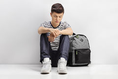 Sad teenage student leaning against a gray wall. Sad teenage student sitting on the floor and leaning against a gray wall Stock Photo