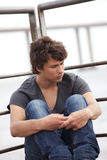 Sad Teenager. Handsome teenager with a sad face sited next to the river royalty free stock images