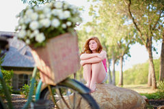 Sad teenager. Beautiful teenage girl sitting alone on a rock in the yard looking sad and upset Royalty Free Stock Photos