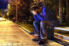 Sad teenager. Sad and lonely teenager with hidden face sitting in the night park Stock Photo