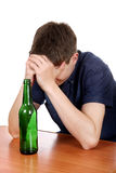 Sad Teenager in Alcohol Addiction. Sad and Depressed Man in Alcohol addiction on Desk Isolated on the White Background royalty free stock photo