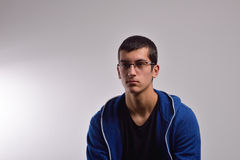 Sad teenager with blue sweatshirt standing against a dirty wall Royalty Free Stock Photo