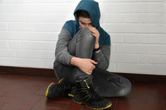 Sad teenager boy. Depressed teenage boy sitting on the floor Stock Images