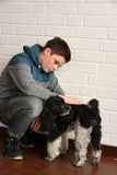 Sad teenager boy. Depressed teenage boy sitting on the floor comforted by his little dog Royalty Free Stock Images
