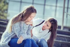 Sad Teenager cries, her girlfriend sympathizes. Sad Female Teen is Crying because of Teenage Problems, and Her Friend Looks Sympathetically at Her, Sitting on Stock Photo